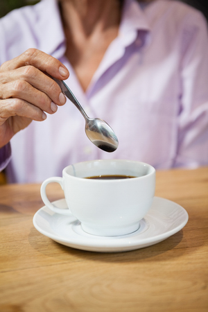 Cropped image of woman stirring coffee while sitting at table in cafe