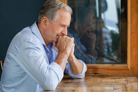 Thoughtful senior man sitting at table in cafe shop Stock Photo