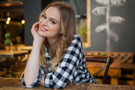 Portrait of young woman sitting at table in cafe shop
