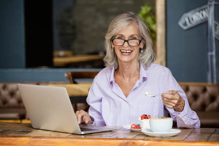 Portrait of senior woman using laptop computer while eating breakfast in cafe shop Stock Photo