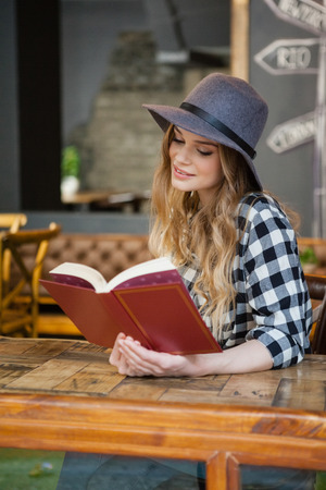 Young beautiful woman wearing hat reading book while sitting at cafe shop