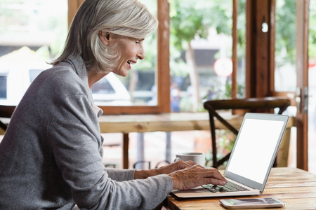 Side view of senior woman using laptop computer while sitting at table in cafe shop