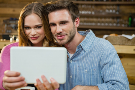 Young couple using digital tablet in café