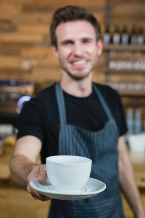 Smiling waiter offering cup of coffee at counter in café Stock Photo