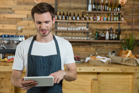 Waiter using digital tablet at counter in café