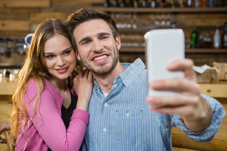 Young couple taking selfie on mobile phone in café