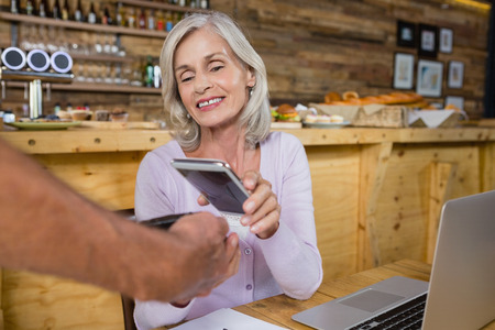 Senior woman making payment through NFC technology on mobile phone in café Stock Photo