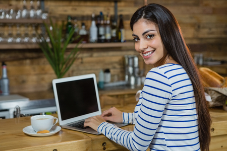 Portrait of woman using laptop at counter in café