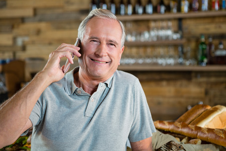 Portrait of senior man talking on mobile phone in café