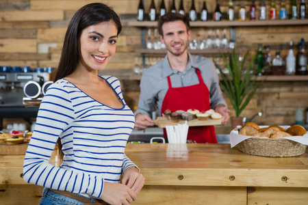Portrait of smiling woman with waiter standing in background in café