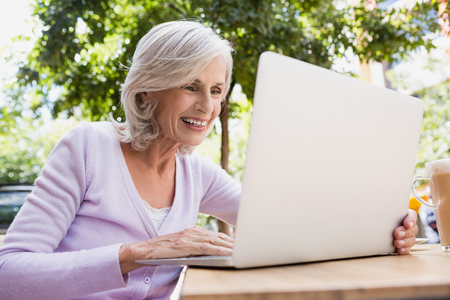 Senior woman using laptop in outdoor café on a sunny day Stock Photo