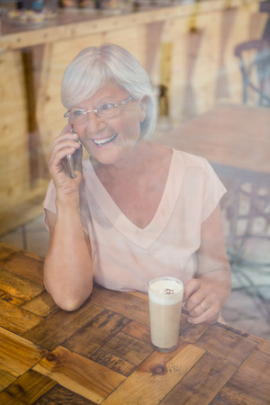 Happy senior woman talking on mobile phone while having cold coffee in café