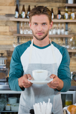 Portrait of smiling waiter serving cup of coffee at counter in cafe