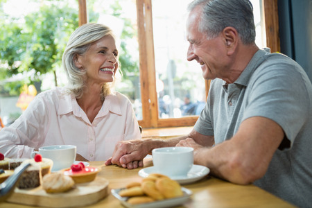 Senior couple interacting with each other in café Stock Photo