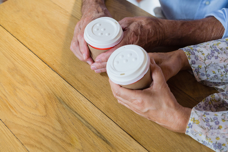 Senior couple holding disposable coffee cup in café Stock Photo