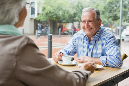 Senior couple sitting with coffee in outdoor cafe
