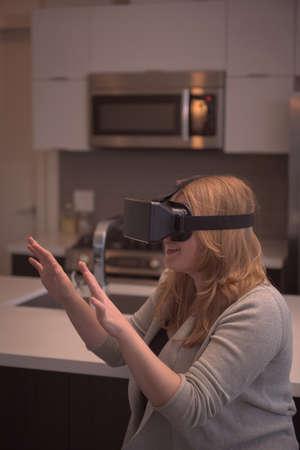 virtual reality simulator: Woman gesturing while enjoying virtual reality simulator in kitchen at home