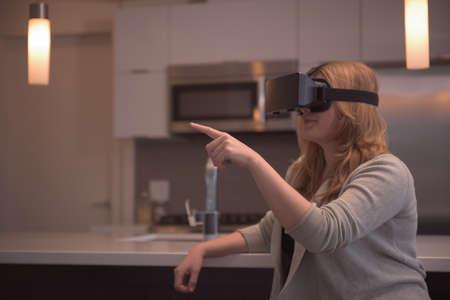 illuminated: Woman gesturing while enjoying virtual reality simulator at home