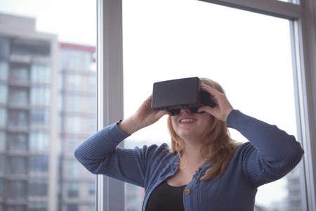 virtual reality simulator: Close-up of woman enjoying virtual reality simulator by window at home