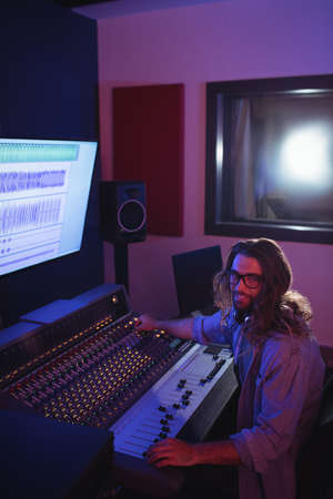 illuminated: Portrait of male audio engineer using sound mixer in recording studio LANG_EVOIMAGES