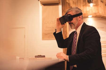 virtual reality simulator: Businessman using virtual reality simulator while sitting at table LANG_EVOIMAGES
