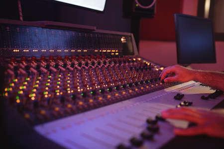 illuminated: Hands of male audio engineer using sound mixer in recording studio