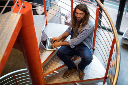 Portrait of sound engineer using laptop on stairs in office