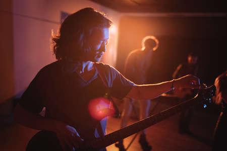 illuminated: Musician adjusting his guitars strings in recording studio