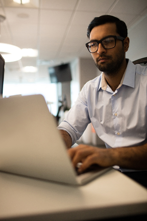 Young businessman working on laptop while sitting at desk in office Stock Photo