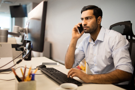 Young businessman talking on mobile phone while using computer in office Stock Photo