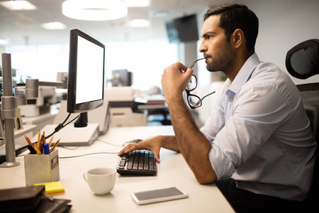 Side view of thoughtful businessman using computer at desk in office