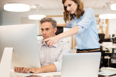 Female colleague assisting businessman working on computer in office Stock Photo