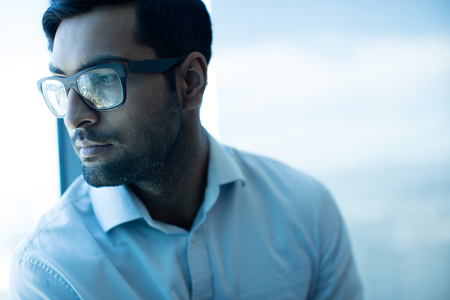 Thoughtful businessman looking away while wearing eyeglasses at office