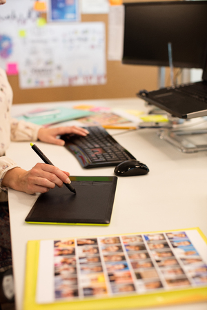 Cropped image of businesswoman working on digitizer at desk in office Stock Photo