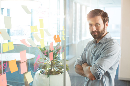 Portrait of young businessman with arms crossed standing by strategy on glass at office