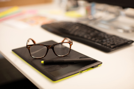 High angle view of eyeglasses on digitizer at desk in office