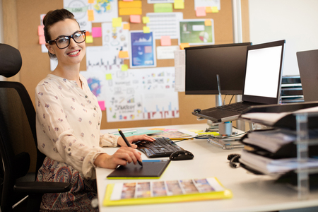 Portrait of smiling businesswoman working on digitizer while using keyboard at desk in office