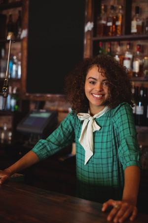 bartending: Portrait of beautiful female bar tender standing at bar counter Stock Photo