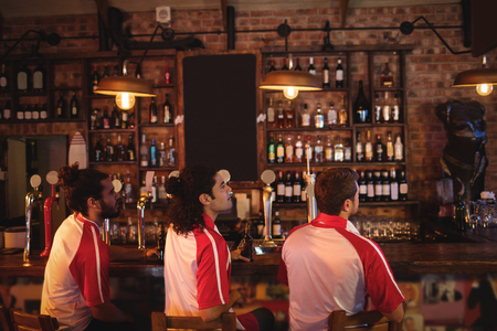 grupo de amigos masculinos viendo partido de fútbol en pub