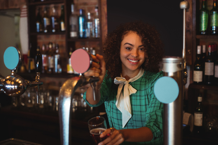 beer pump: Portrait of waitress using beer tap at counter in pub