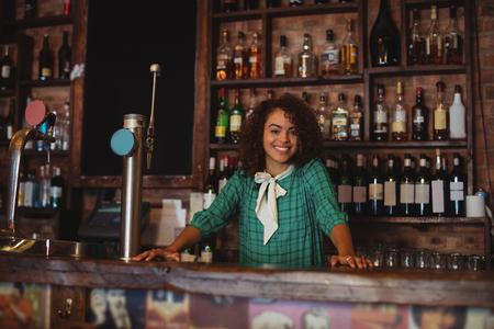 beer pump: Portrait of beautiful female bar tender standing at bar counter Stock Photo