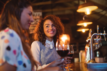 beer pump: Young women interacting with each other at counter in pub