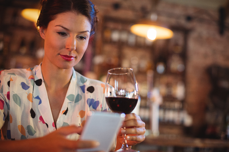 Young woman using mobile phone while having wine in pub Stock Photo