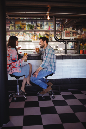 stool: Happy couple interacting while having beer at counter in bar