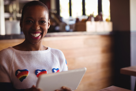 mid morning: Portrait of happy woman using digital tablet in restaurant