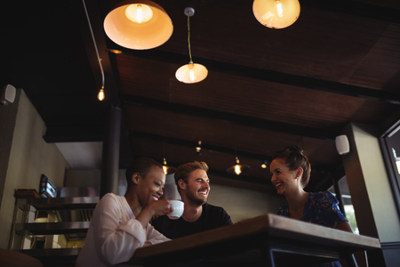 Happy friends interacting while having coffee in restaurant Stock Photo