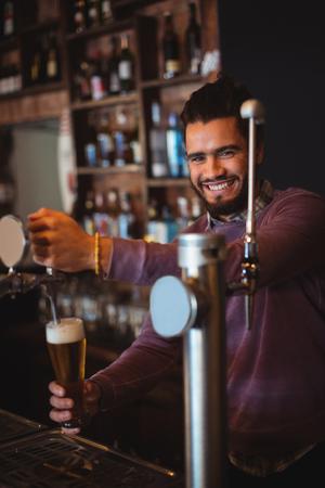hotel staff: Bar tender filling beer from bar pump at bar counter Stock Photo