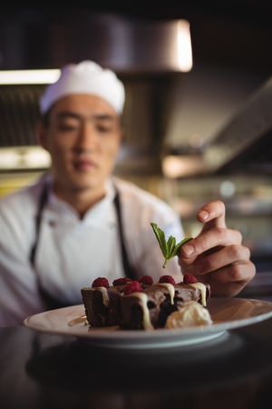 Close-up of male chef garnishing dessert plate in commercial kitchen Stock Photo