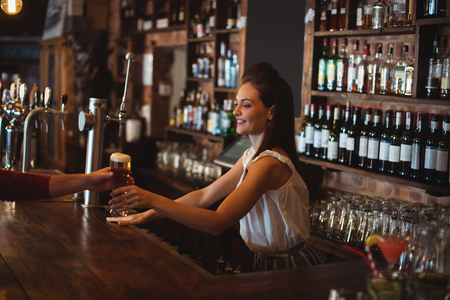 hotel staff: Female bar tender giving glass of beer to customer at bar counter Stock Photo