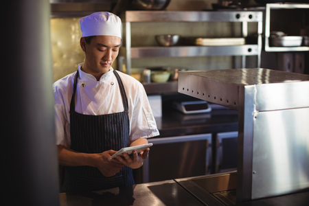 Smiling chef using digital tablet in the commercial kitchen Imagens - 77357454